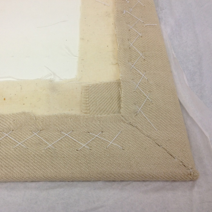 mount board with glued calico and herringbone stitched exbroidery piece